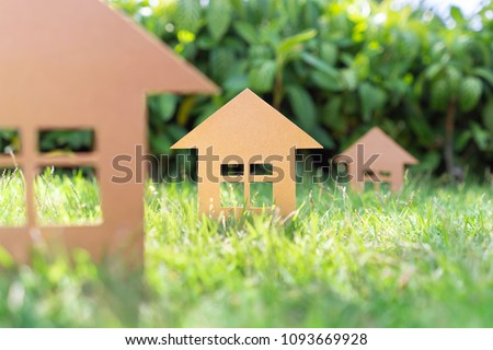 Three carboard houses on a grass lawn sun trees #1093669928