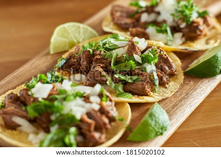 Photo of  three carne asada mexican street tacos in corn tortilla with lime