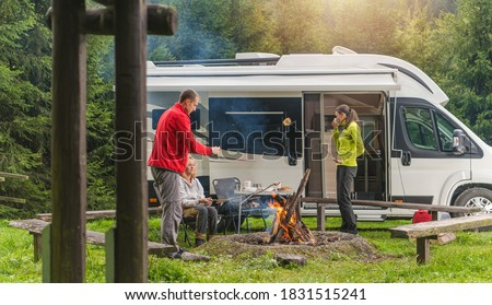 Three Caucasian Friends in Their Late 30s, One Men and Two Woman Having Fun on Wilderness Camping with Modern RV Camper Van. Grilling Bread and Polish Sausage on Campfire.