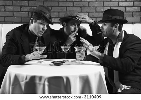 Three Caucasian prime adult males in retro suits sitting at table drinking and smoking and talking.