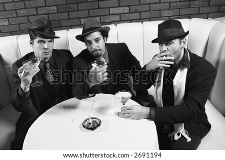 Three Caucasian prime adult males in retro suits sitting at table with cocktails looking at viewer.