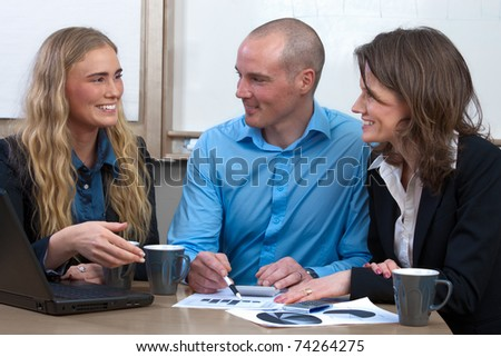 Three caucasian professionals discussing strategies in a meeting at the conference room