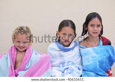 three caucasian sisters with blue eyes wrapped up in a beach towel all with different expressions on their faces