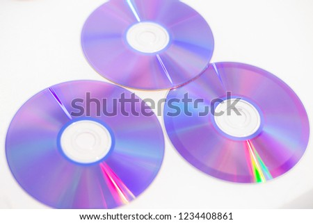 Three CDs/DVDs - Blank recordable DVDs (DVD-R) purple discs on white background #1234408861