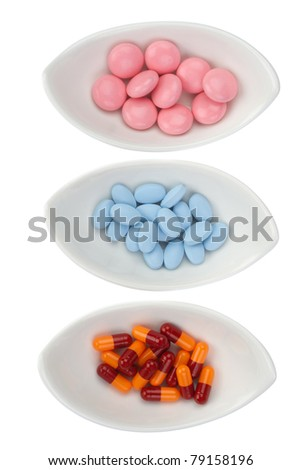 Three ceramic bowls with color pills