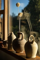 Three ceramic vase flagon front to big sunny window and its reflection