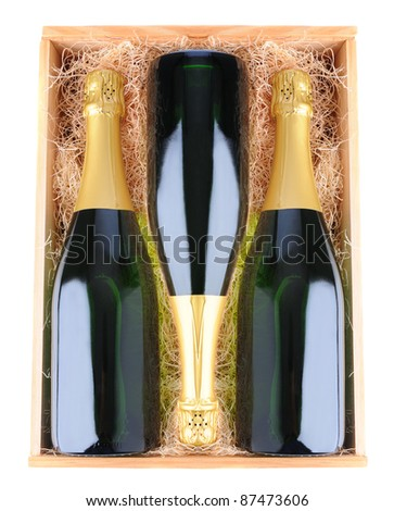 Three Champagne bottles in a wooden case with straw packing material. Overhead view over a white background