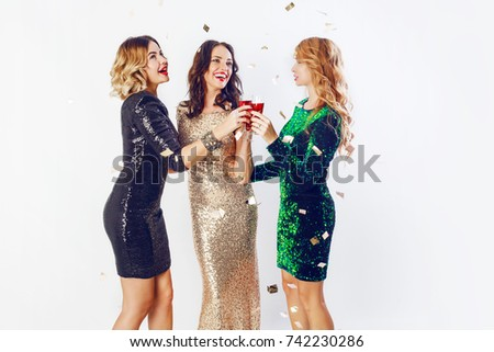 Three charming  girls spending time on new year or birthday party. Holding glass of champagne , dancing and enjoying   evening. Studio image.  White background.