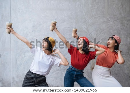 Three cheerful asian female teenager friends with pearl milk tea cup laughing together against grey concrete background
