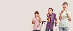 Three cheerful disabled children with Down syndrome and cerebral palsy smiling while blowing soap bubbles, standing together isolated over white background. Lifestyle of special children concept