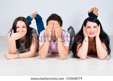Three cheerful friends lying down on wooden floor and gesturing speak,see and hear no evil