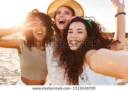 Three cheerful girls friends in summer clothes taking a selfie at the beach