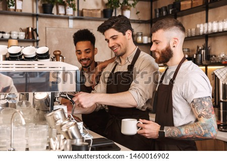 Three cheerful male baristas standing at the coffee shop counter indoors