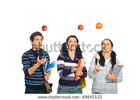 Three cheerful students throw up apples and having fun isolated on white background