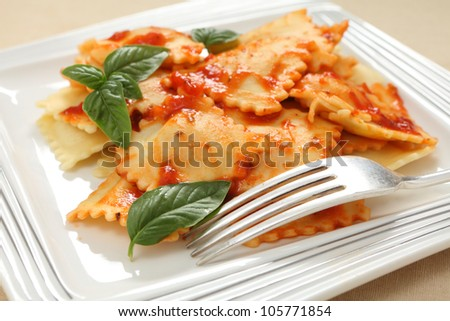 Three cheese ravioli in a pasta sauce with herbs close-up