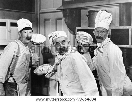 Three chefs holding pies for a fight in the kitchen