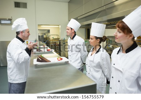 Three chefs presenting their dessert plates to the head chef in busy kitchen Stock photo ©