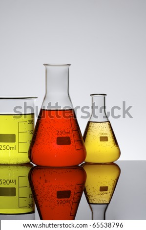three chemical beakers with colored liquid and a white background