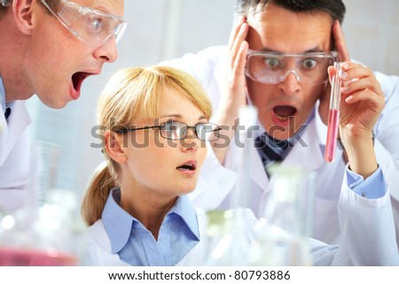 Three chemists looking shocked at a tubing and shouting in joy