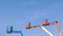 Three Cherry Picker machines against a blue sky