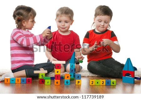 Three children are playing on the floor together