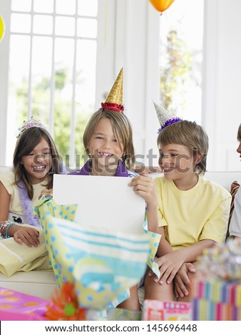 Three children at birthday party as one open the gift
