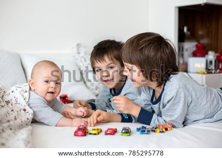 Three children, baby and his older brothers in bed in the morning, playing together, laughing and having a good time, sharing special moment, bonding #785295778