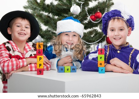 "Three children dressed in carnival suits are greeting with sigh ""happy new year"" made with blocks; isolated on the white background"