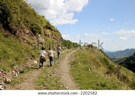 Three children hiking along a mountain path