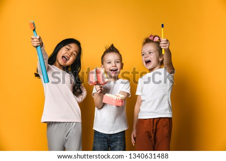 Three children hold toothbrushes, girls show their toothbrushes and the boy holds a model of the jaw with white teeth. The concept of health, oral hygiene, people and beauty.