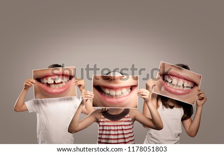 three children holding a picture of a mouth smiling #1178051803