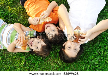 Three children laying on green grass on ground and eating sandwiches and smiling, healthy food, good friendship and love and happiness without limit :)