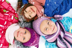Three children lie on the snow in winter and looking upwards