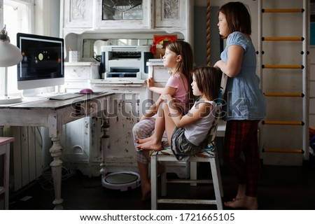 three children look at the monitor, watch cartoons or educational programs on computers, an authentic home lifestyle