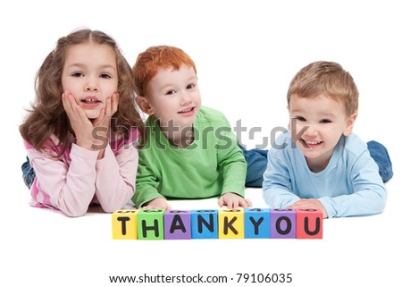 Three children lying saying thankyou with kids letter blocks. Isolated on white.
