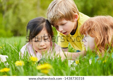 Three children on a meadow with a magnifying glass as a curious explorer and explorer #1438730318