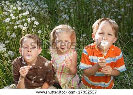 three children playing outdoors in a dandelion patch