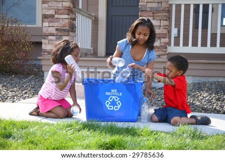 Three children putting items into recycle bin