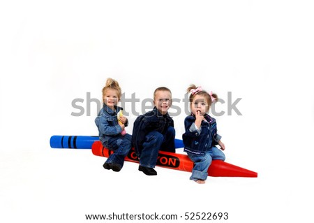 Three children sit on two giant colors in red and blue.  They are dressed in denim jackets and jeans and are having a ball playing in an all white room.
