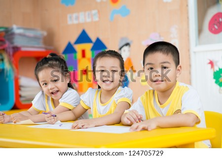 Three children sitting behind the desk and smiling