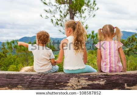 three children sitting on the bench against the backdrop of the mountains