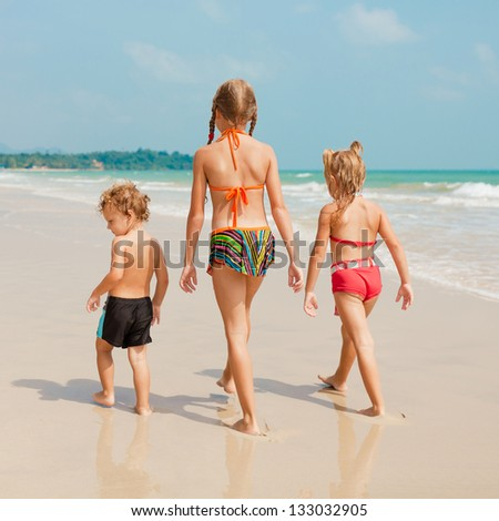 three children walking on white beach