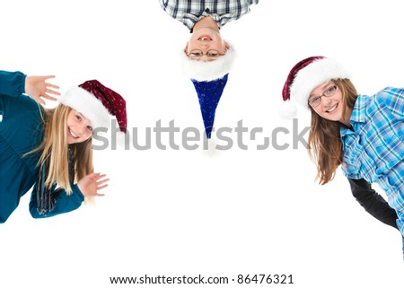 three children with christmas hats on white girls sidewise boy overhead