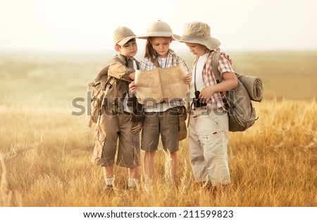 Three children with maps and travel backpacks on steppe valleys in summer at sunset