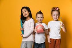 Three children with toothbrushes and a Dental implant model  stand over yellow background wall and smile rejoicing at the camera.The concept of health, oral hygiene, people and beauty.