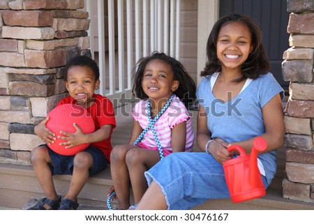 Three children with toys on porch