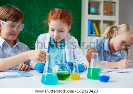 Three children working with chemical liquids at lesson - stock photo