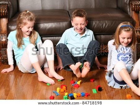 three childrens playing with blocks with their feet - stock photo