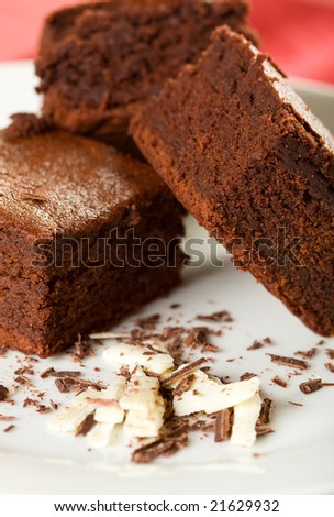 Three Chocolate Brownies on a white plate with dark and white chocolate shavings