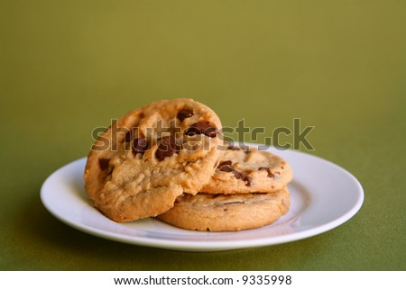 Three Chocolate Chip Cookies on a Plate on a Green Background